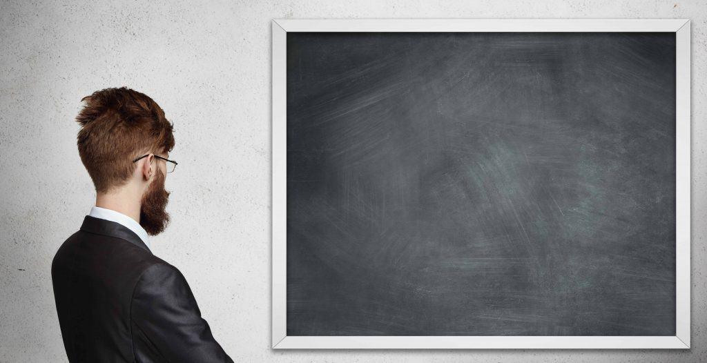 Man looking at blank blackboard
